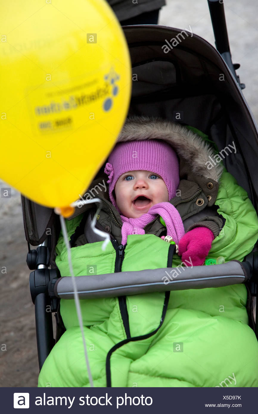 46514446e Essen, Germany, a small child in a stroller with a yellow balloon - Stock