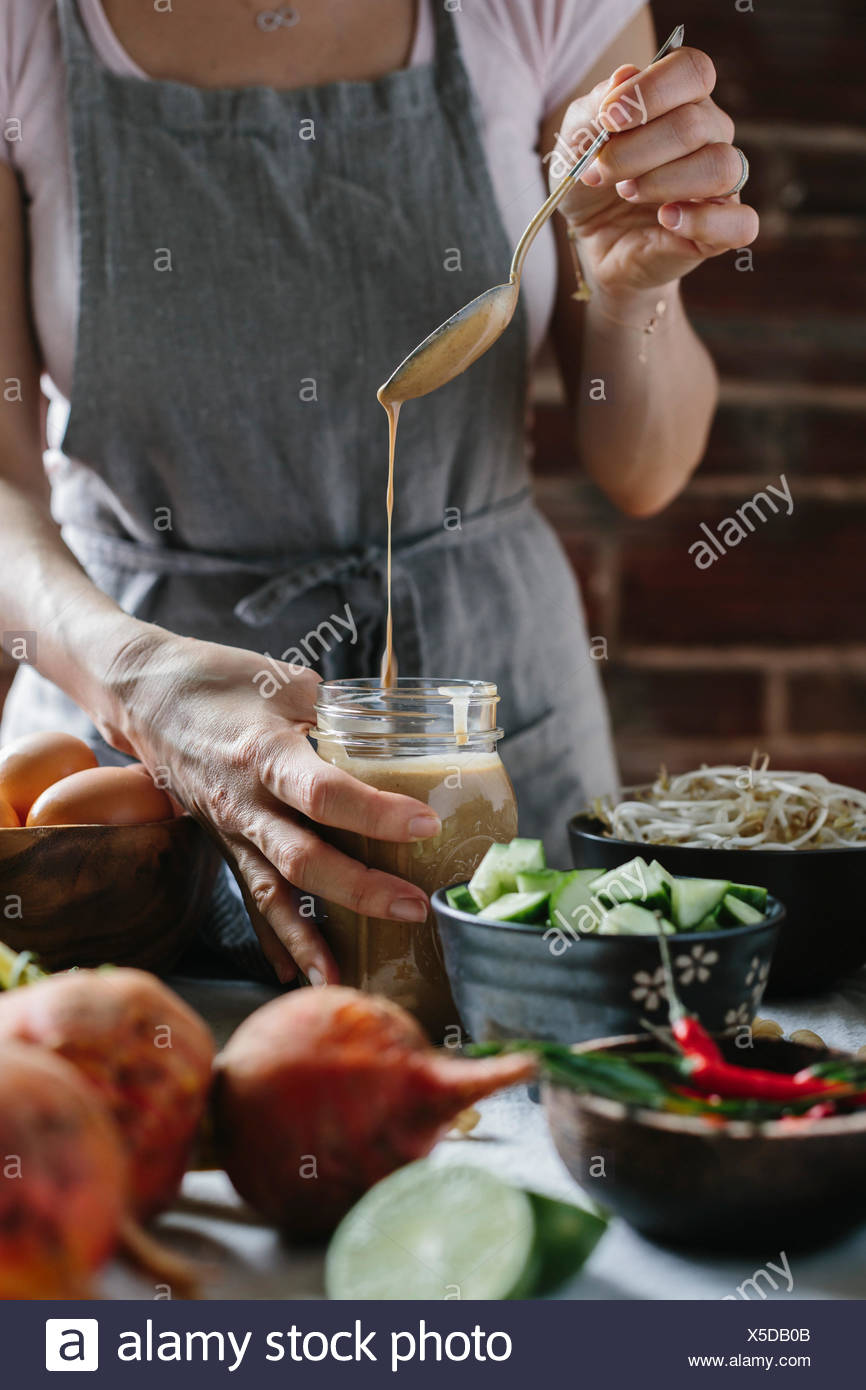 A woman is pouring warm peanut sauce into a jar. - Stock Image