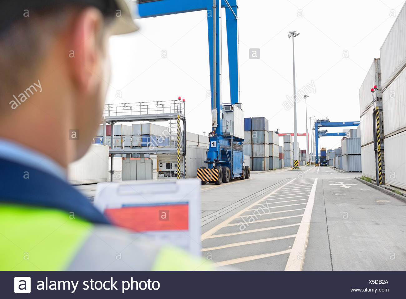 Male supervisor with clipboard in shipping yard - Stock Image