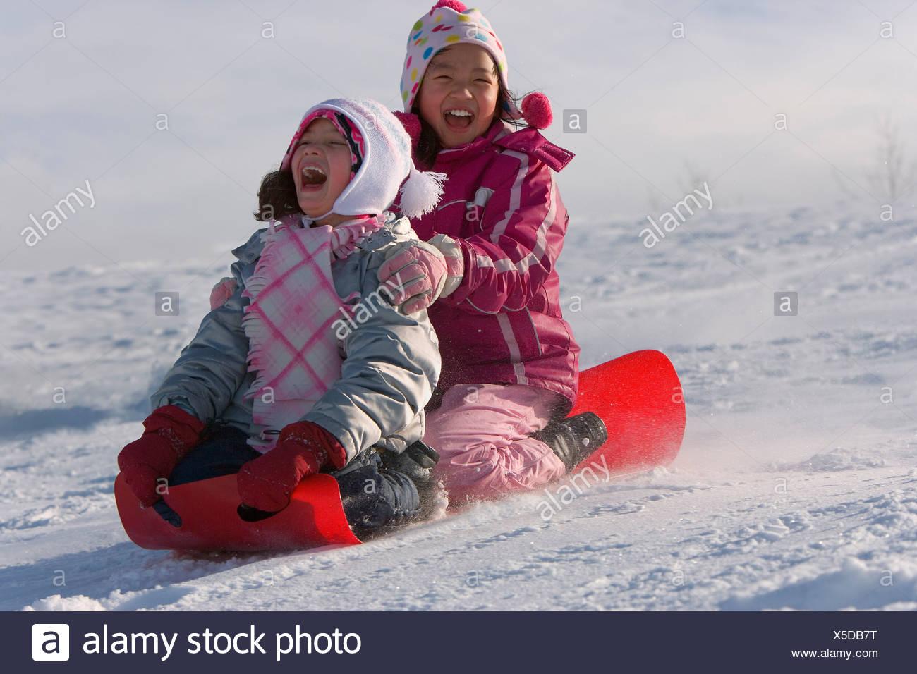 Children tobogganing - Stock Image