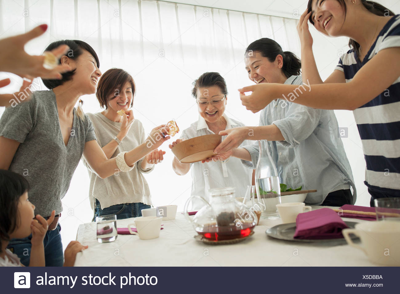 Three generation family laughing at mealtime - Stock Image