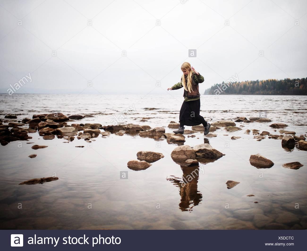 Sweden, Dalarna, Young girl (8-9) walking on stones at lake Siljan - Stock Image