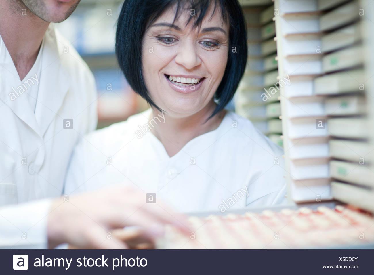 Dental technicians choosing tooth veneers in lab - Stock Image