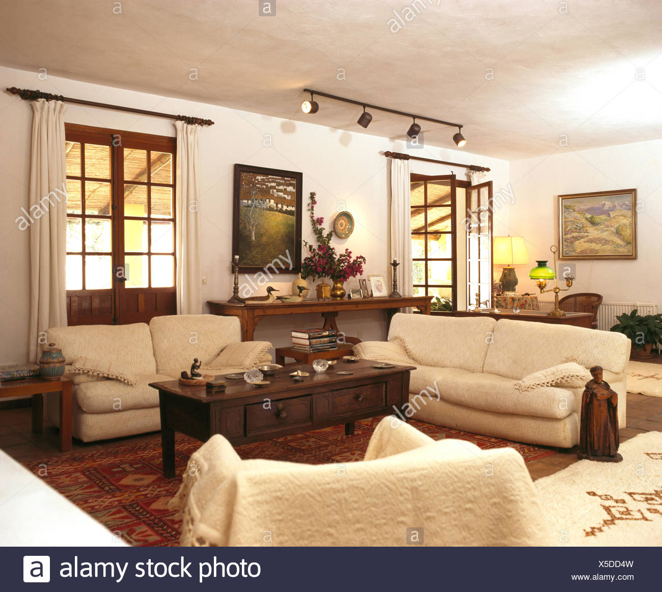 Cream sofas and dark wood coffee table in living room of ...