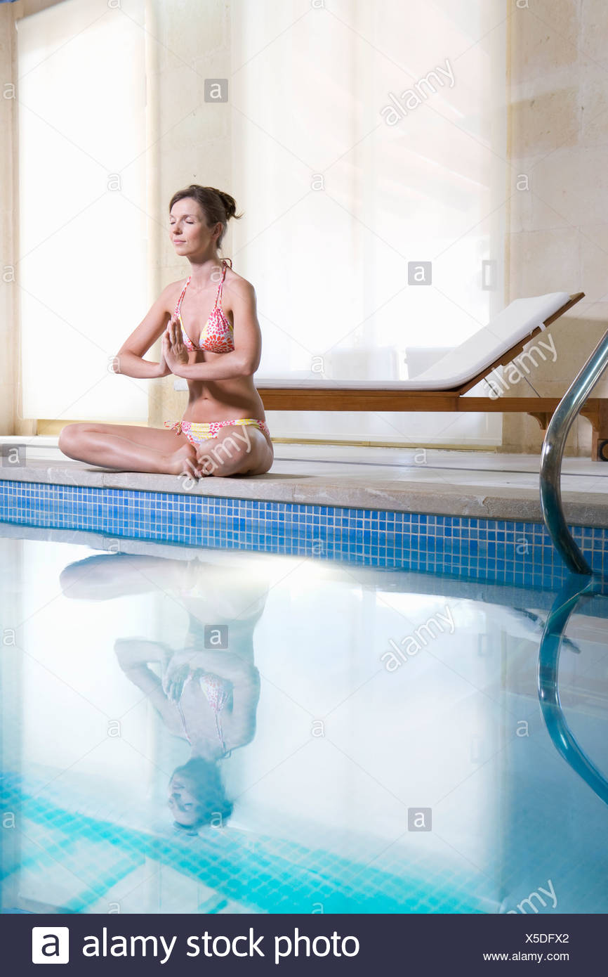 Woman meditating in lotus pose and meditating at poolside - Stock Image