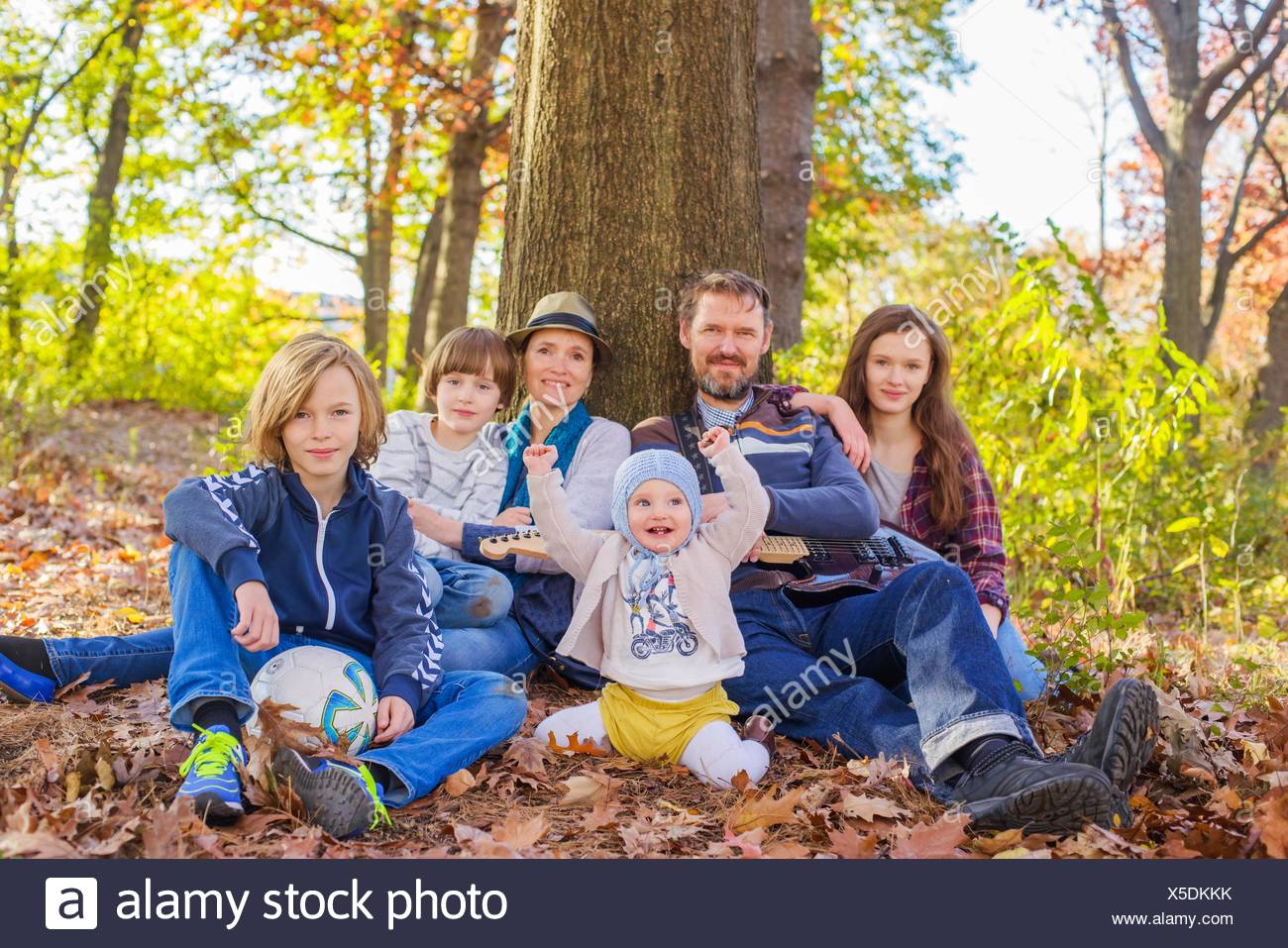 Portrait of family sitting in forest, beside tree Stock Photo