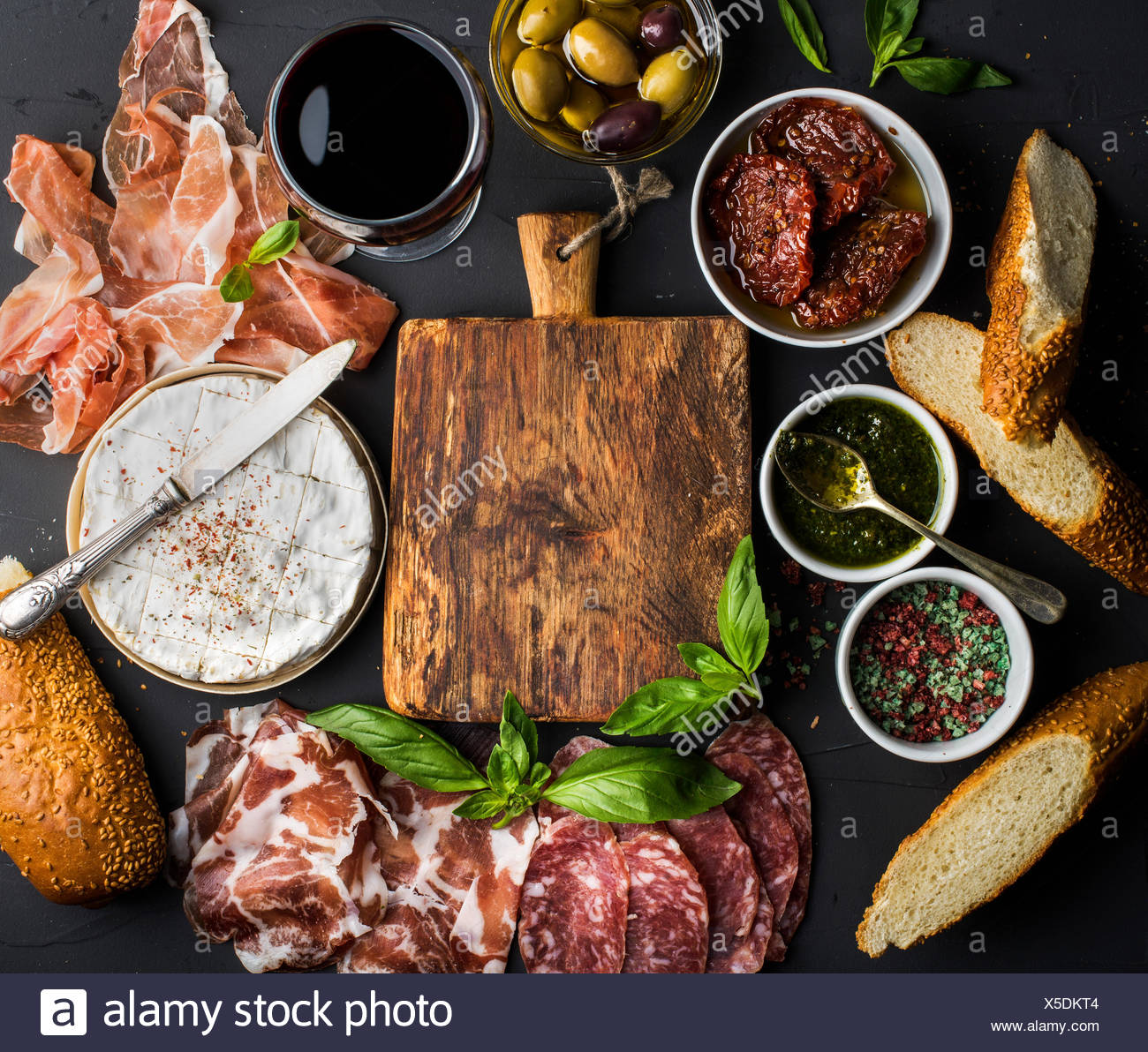 Wine snack set with empty wooden board in center. Glass of red, meat selection, mediterranean olives, sun-dried tomatoes, baguet - Stock Image