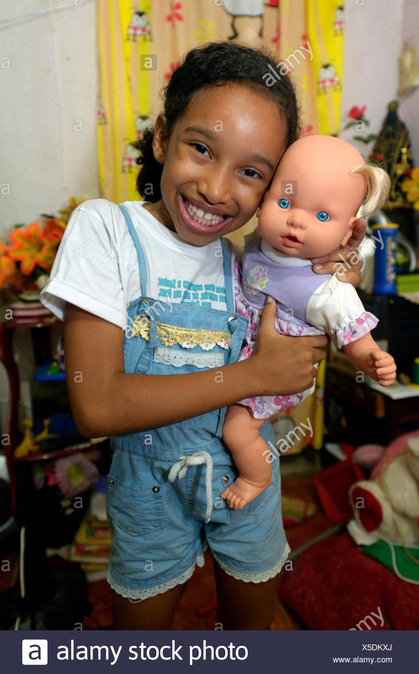 Girl, smiling, holding a doll in an apartment in a slum or favela, Jacarezinho favela, Rio de Janeiro, Rio de Janeiro State - Stock Image