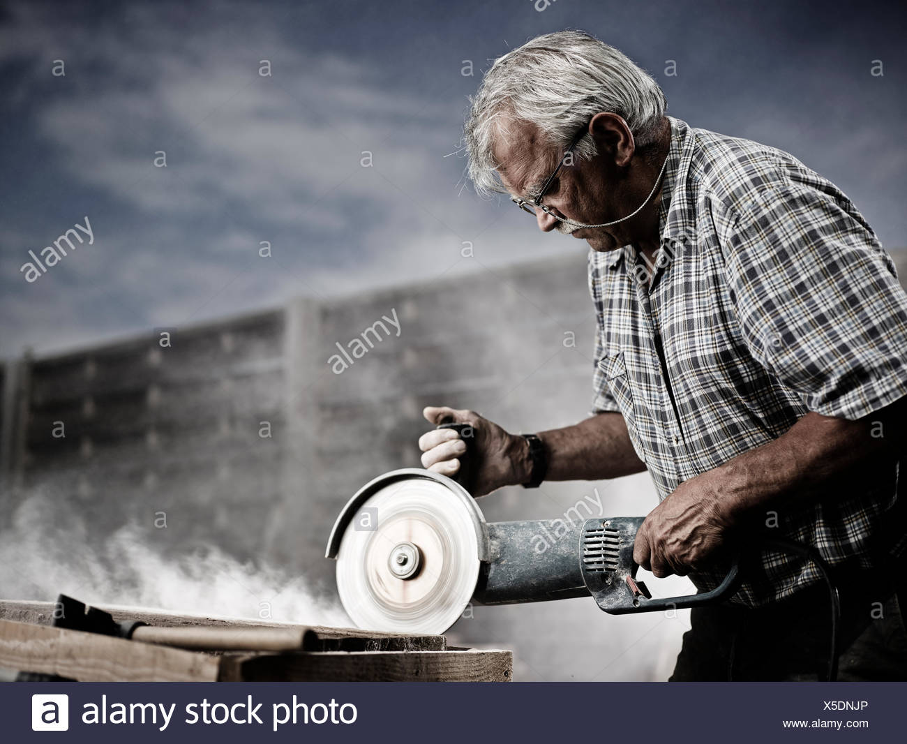 Stonemason cutting a stone slab with an angle grinder with a cutting disc, Reith im Alpbachtal, Kufstein District, North Tirol - Stock Image