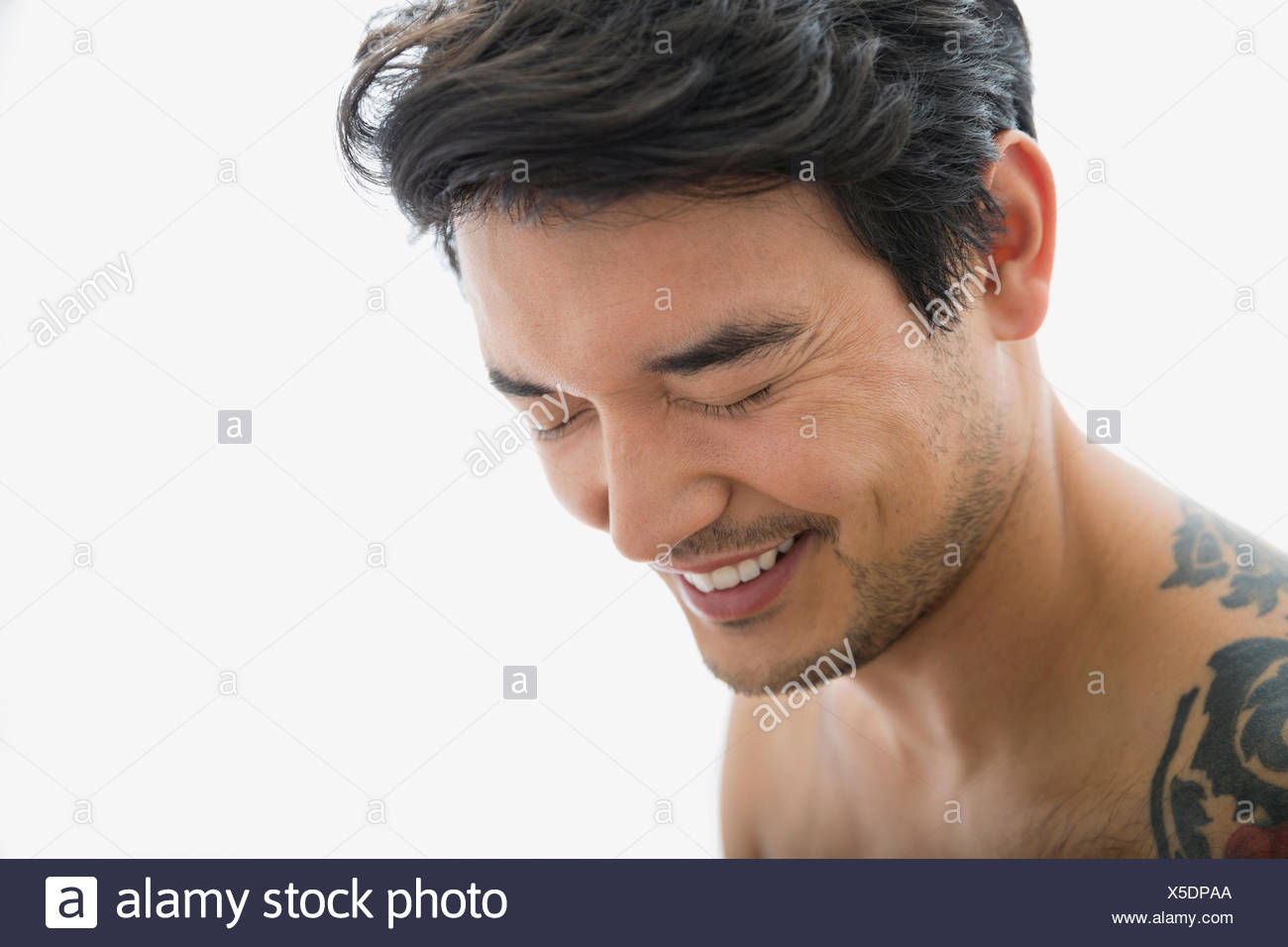 Bare chested man laughing with eyes closed - Stock Image