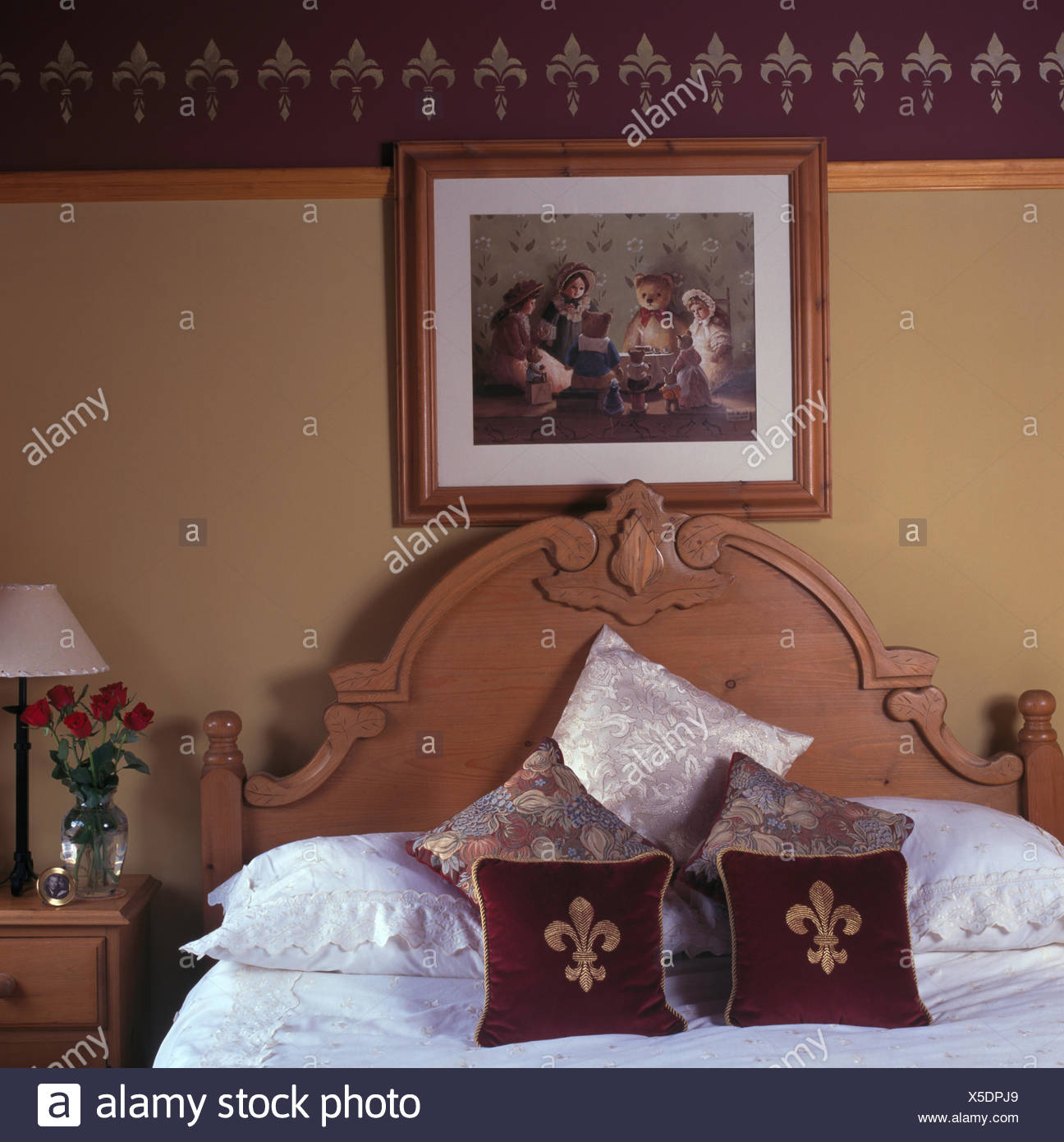 Picture on wall above carved pine bed with velvet fleur-de-lis motif cushions in nineties bedroom with stenciled border - Stock Image