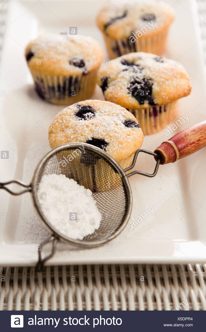 Blueberry Muffins on a Platter with Powdered Sugar in a Sifter - Stock Image