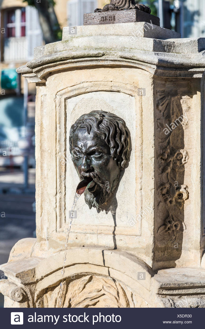 Stone Aix En Provence old water fountain with greek roman face at faucet in aix en