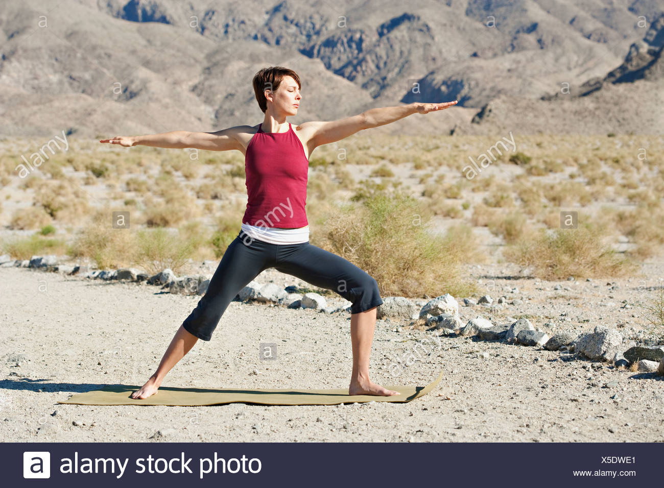 USA, California, La Quinta, Woman standing in yoga warrior pose in desert landscape - Stock Image
