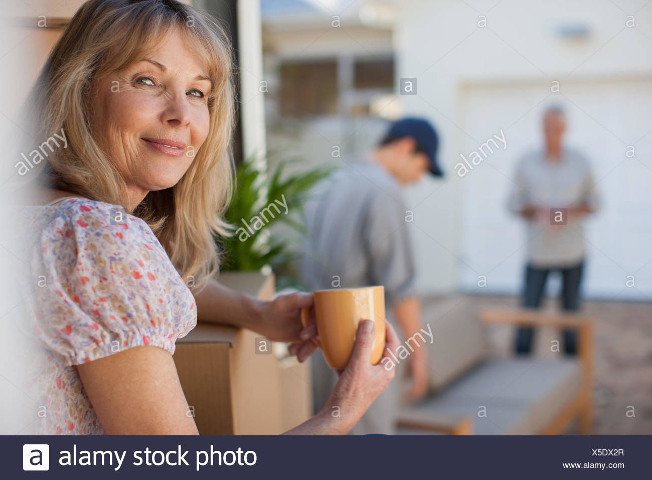 Mover helping couple move into new home - Stock Image