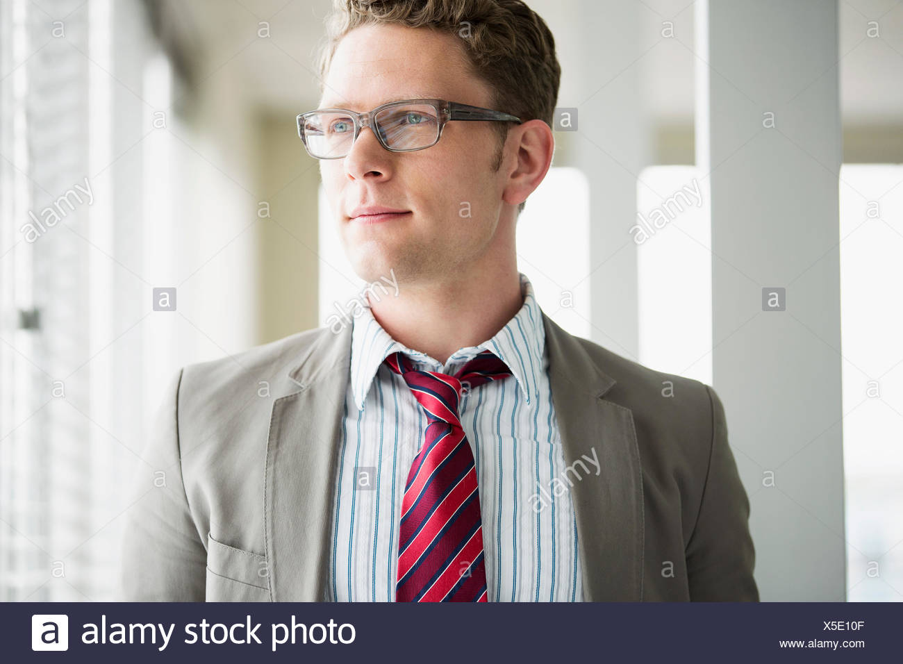 mid-adult businessman gazing out window - Stock Image