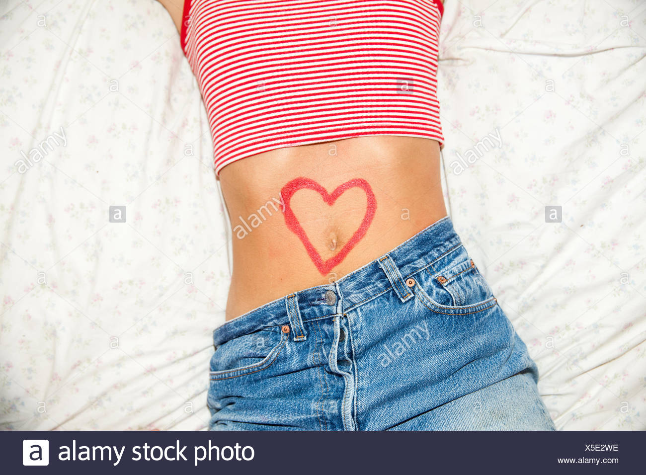 Midsection of woman with heart drawing on stomach - Stock Image