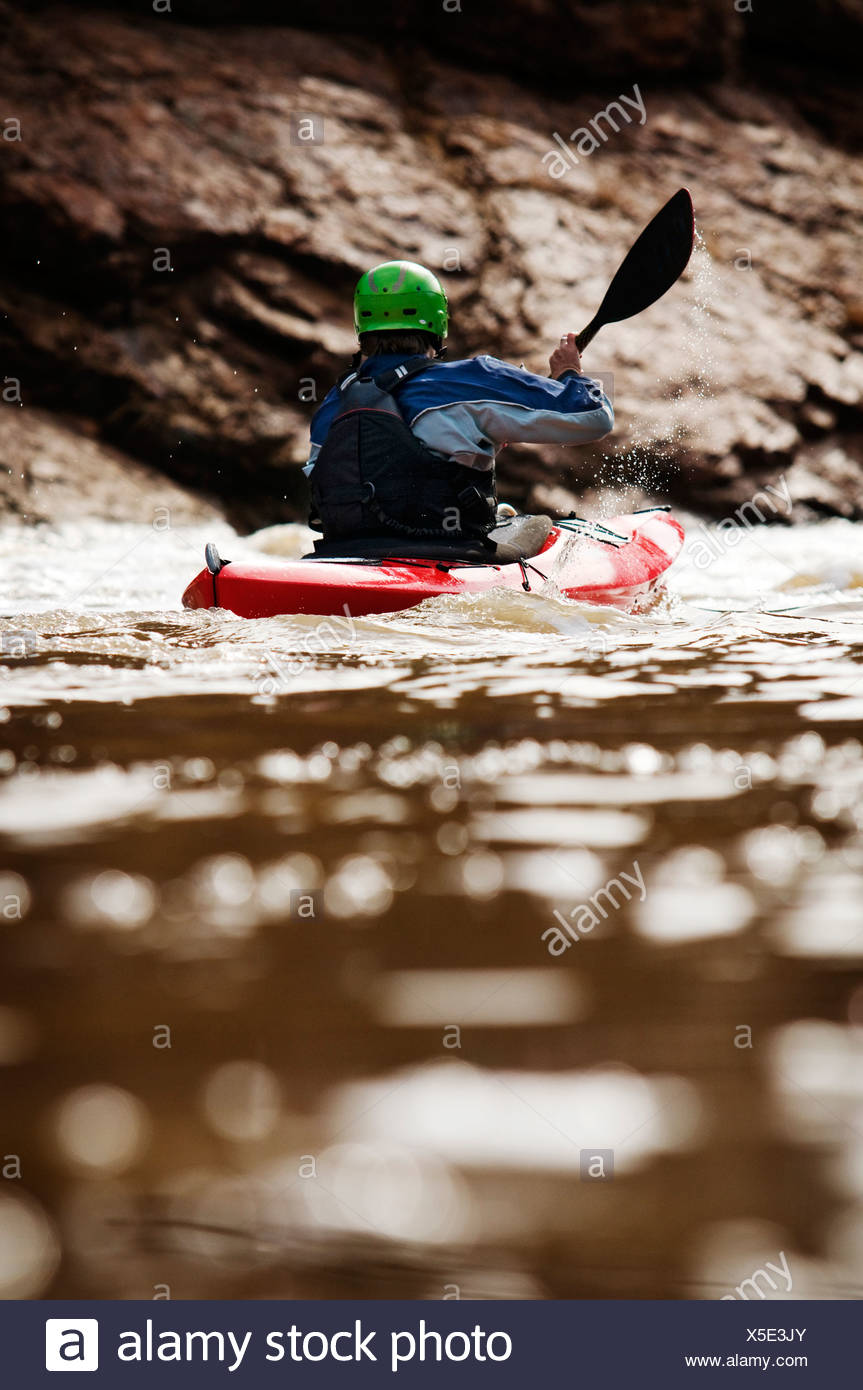 A middle age man paddles his whitewater kayak down the Salt River in Arizona. - Stock Image