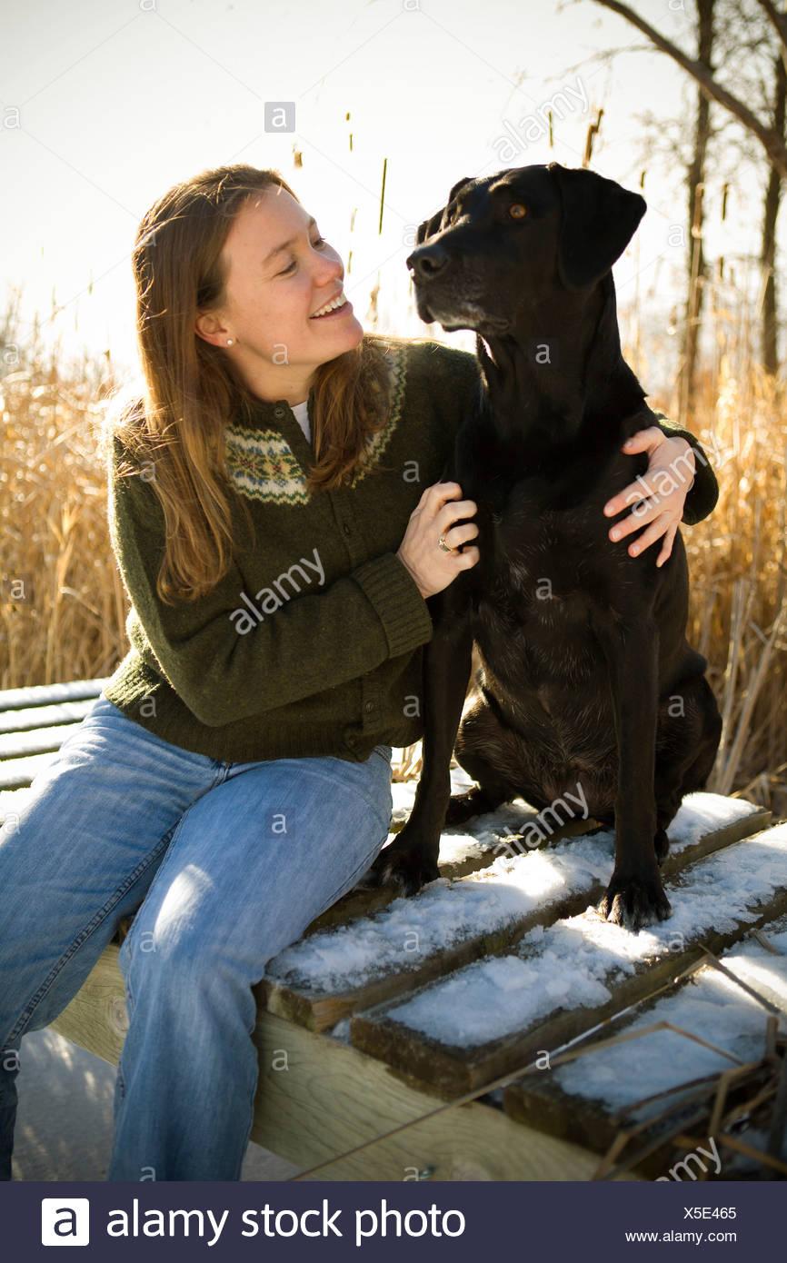 Woman petting her dog - Stock Image