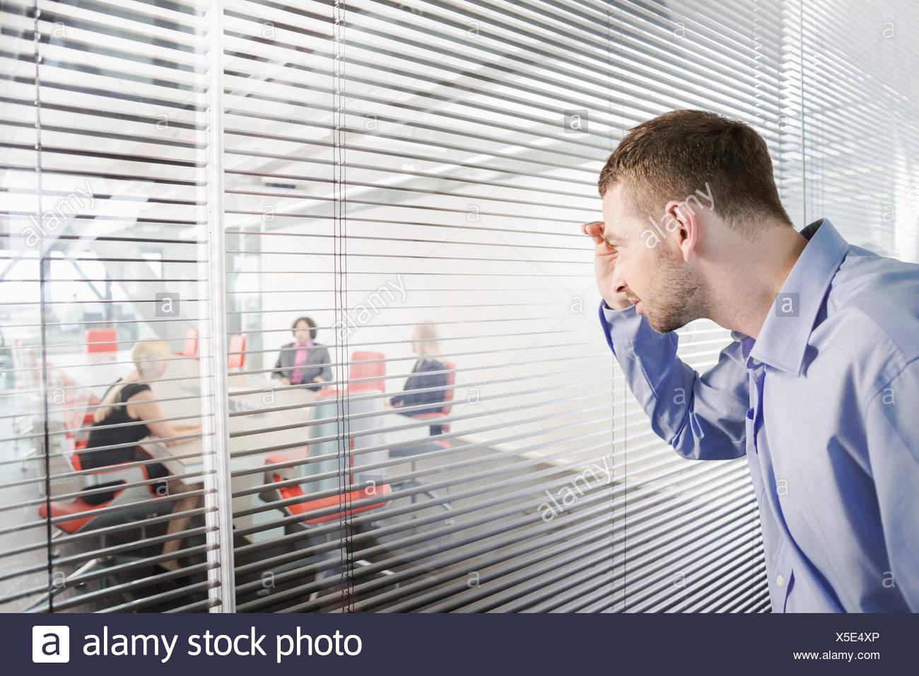Man peering through window blinds - Stock Image