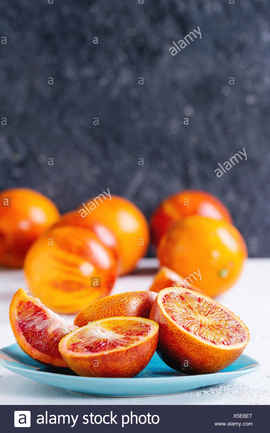 Sliced and whole ripe juicy Sicilian Blood oranges fruits on ceramic plate over white and gray concrete texture background. Copy space Stock Photo