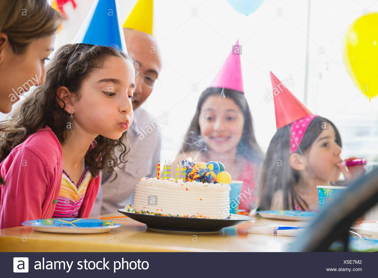 Little girl blowing out candles at birthday party - Stock Image