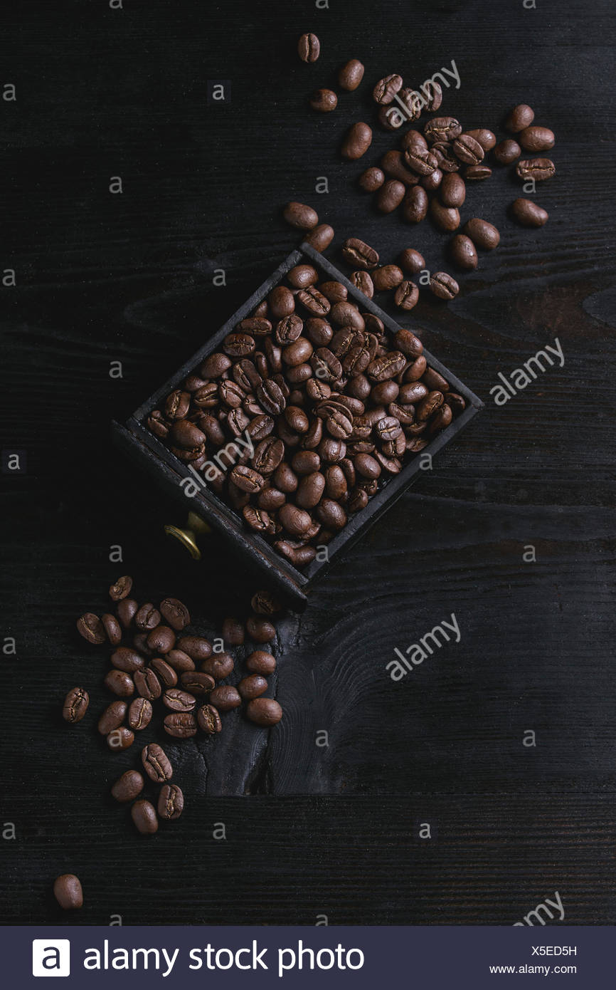 Roasted coffee beans in wood box over black wooden burnt background. Top view with space. - Stock Image