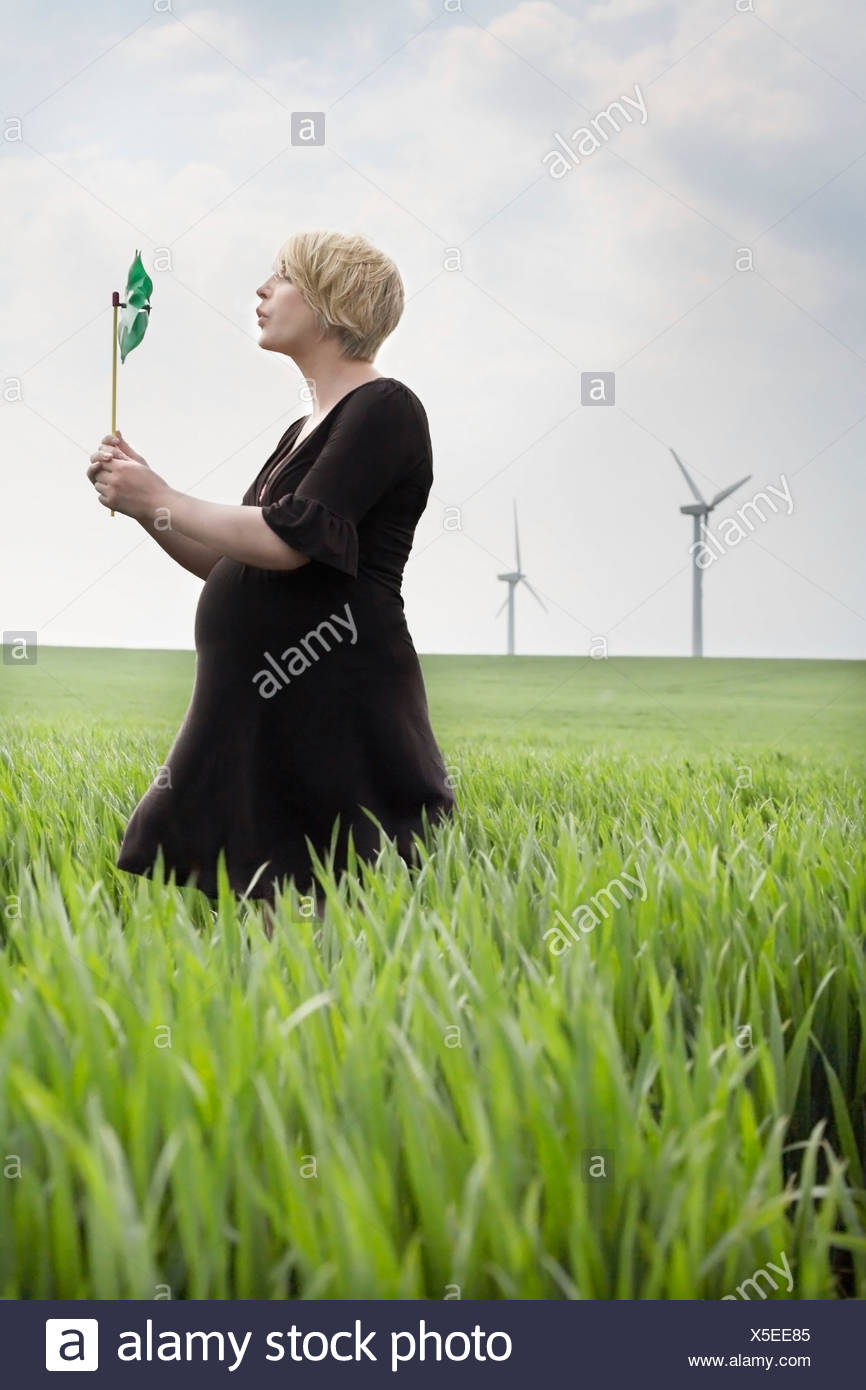 Pregnant woman blowing a windmill - Stock Image