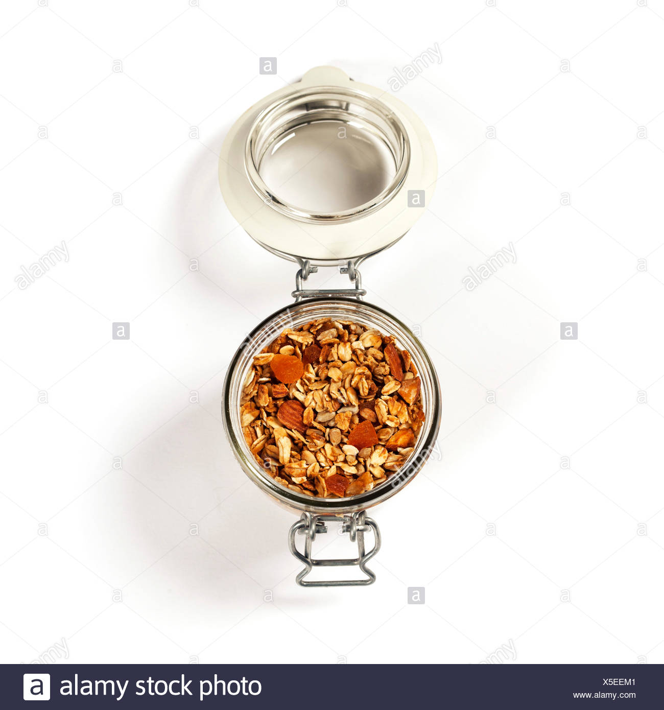 Homemade oatmeal granola with fruits and nuts in a glass jar on white background - Stock Image