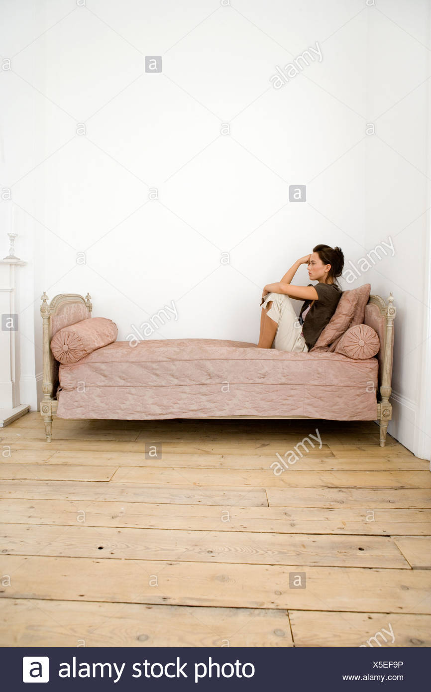 A young woman sitting on a bed - Stock Image