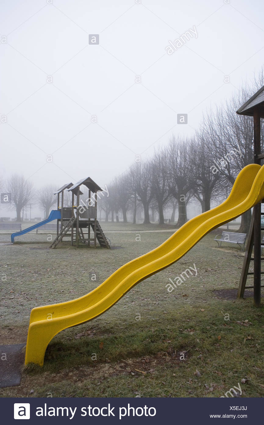 Children's playground, wooden tower, children's slides, fog, deserted, playground, plastic children's slides, yellow, blue, climbing tower, woodwork, season, autumn, trees, bald, exit, dreary, saddles, meadow, foliage, - Stock Image