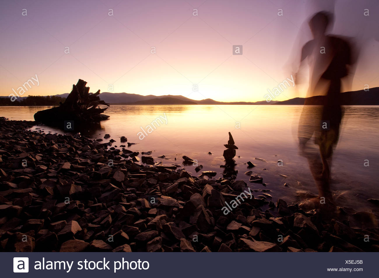 A male figure watching sunset over a lake and mountains in Idaho. - Stock Image