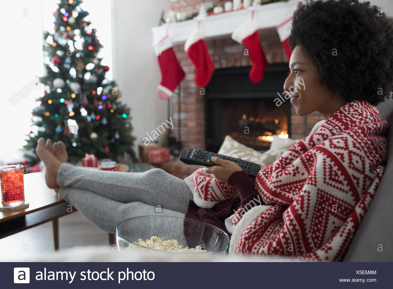 Young woman in pajamas watching TV in Christmas living room - Stock Image