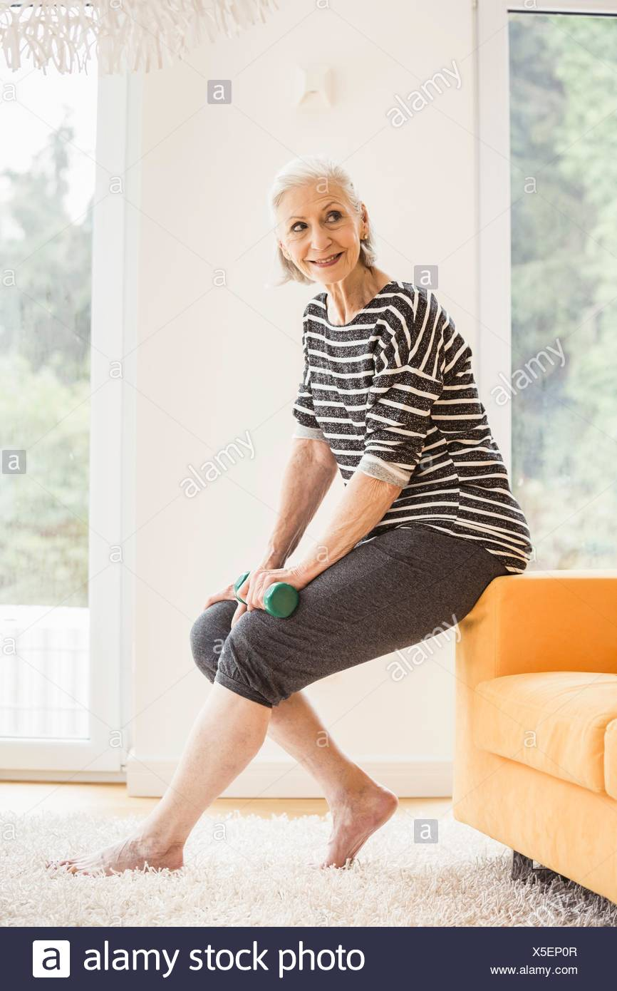 Senior woman sitting on sofa with dumbbell - Stock Image