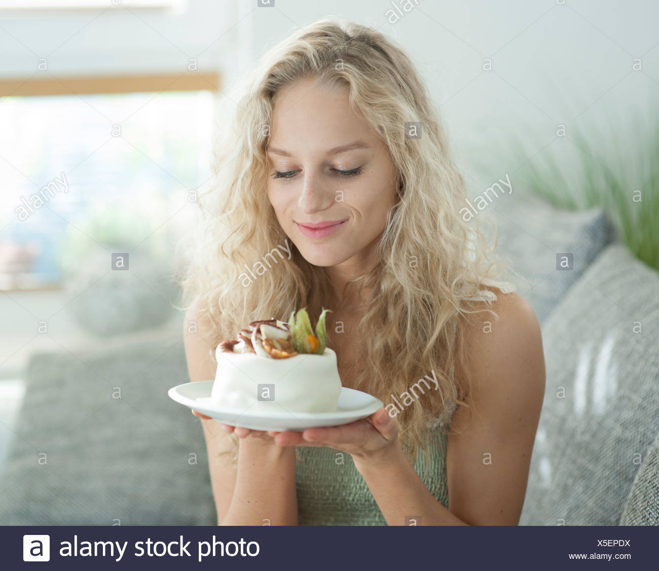 Beautiful young woman looking at tempting cake in house Stock Photo