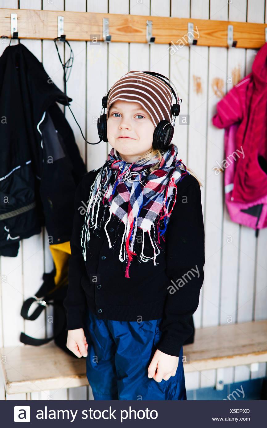 Girl (6-7) with headphones standing in dressing room - Stock Image