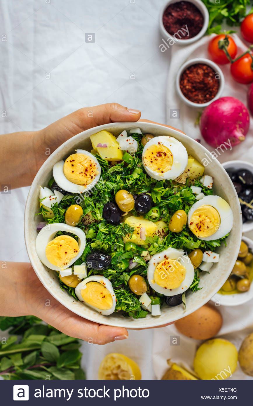 A woman holding a bowl of Mediterranean style potato salad with herbs and hard boiled eggs accompanied by black and green olives, red onion, sumac and - Stock Image