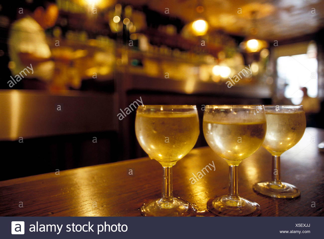 Glasses of white wine on bar counter - Stock Image
