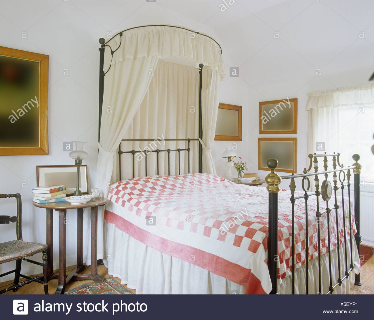 antique brass bed wrought iron metal canopy with white voile drapes on antique brass bed pinkwhite quilt in country bedroom wooden bedside table pink