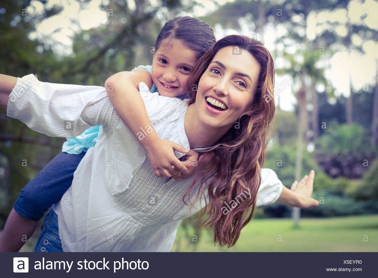 Happy little girl getting a piggy back from mother in the park - Stock Image