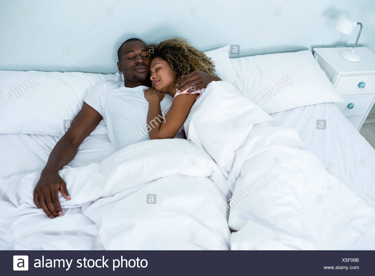 Young couple sleeping together on bed - Stock Image