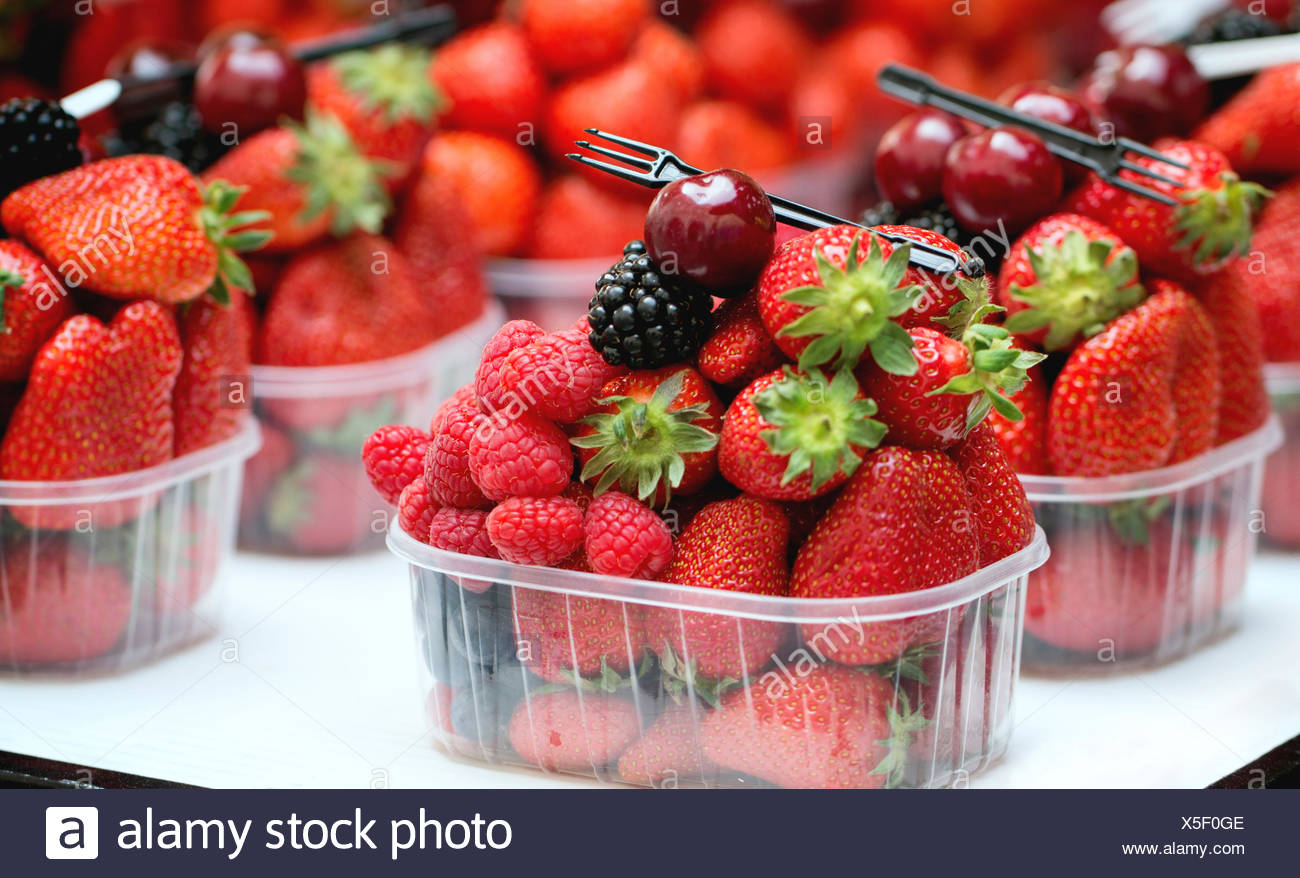 Mix of fresh ripe berries raspberry, strawberry, blackberry and blueberry in plastic boxes with disposable fork in market - Stock Image