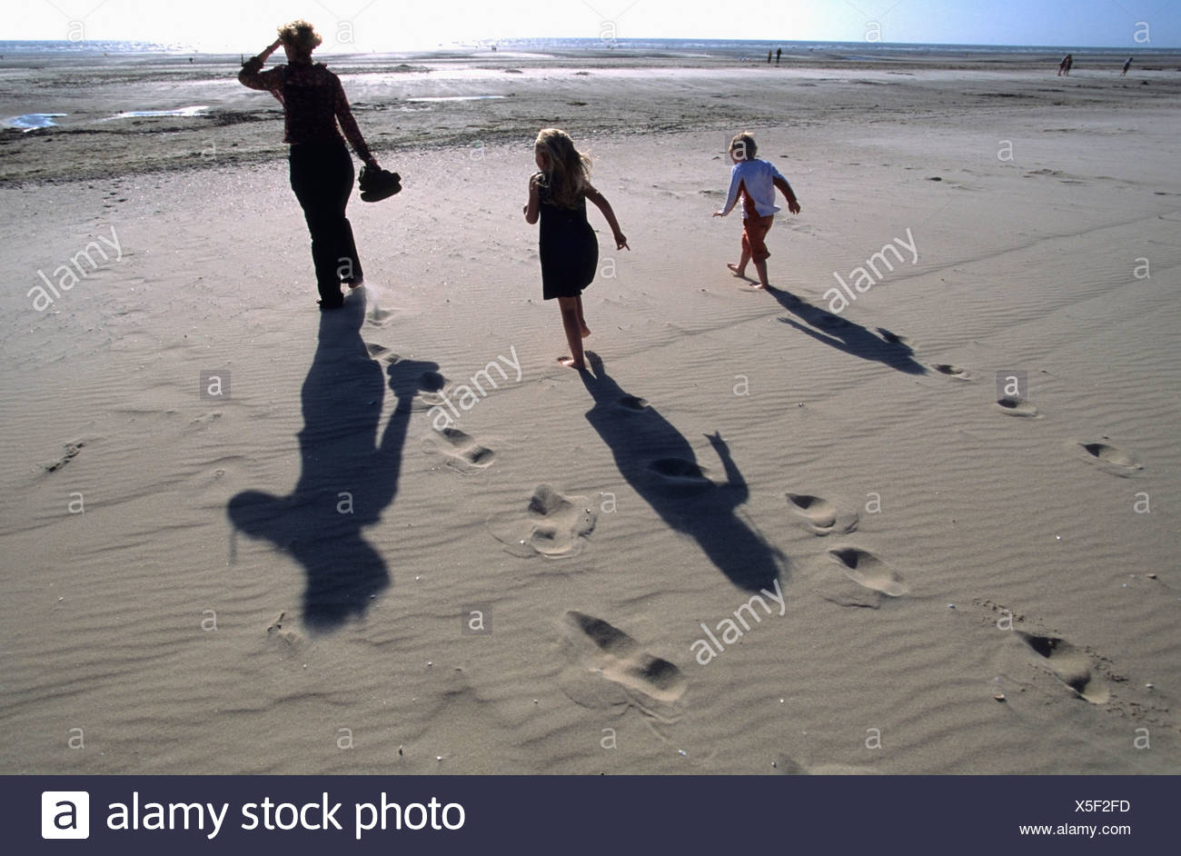 Mother and her children walking barefooted on the beach into the sun; Le Touquet, France - Stock Image