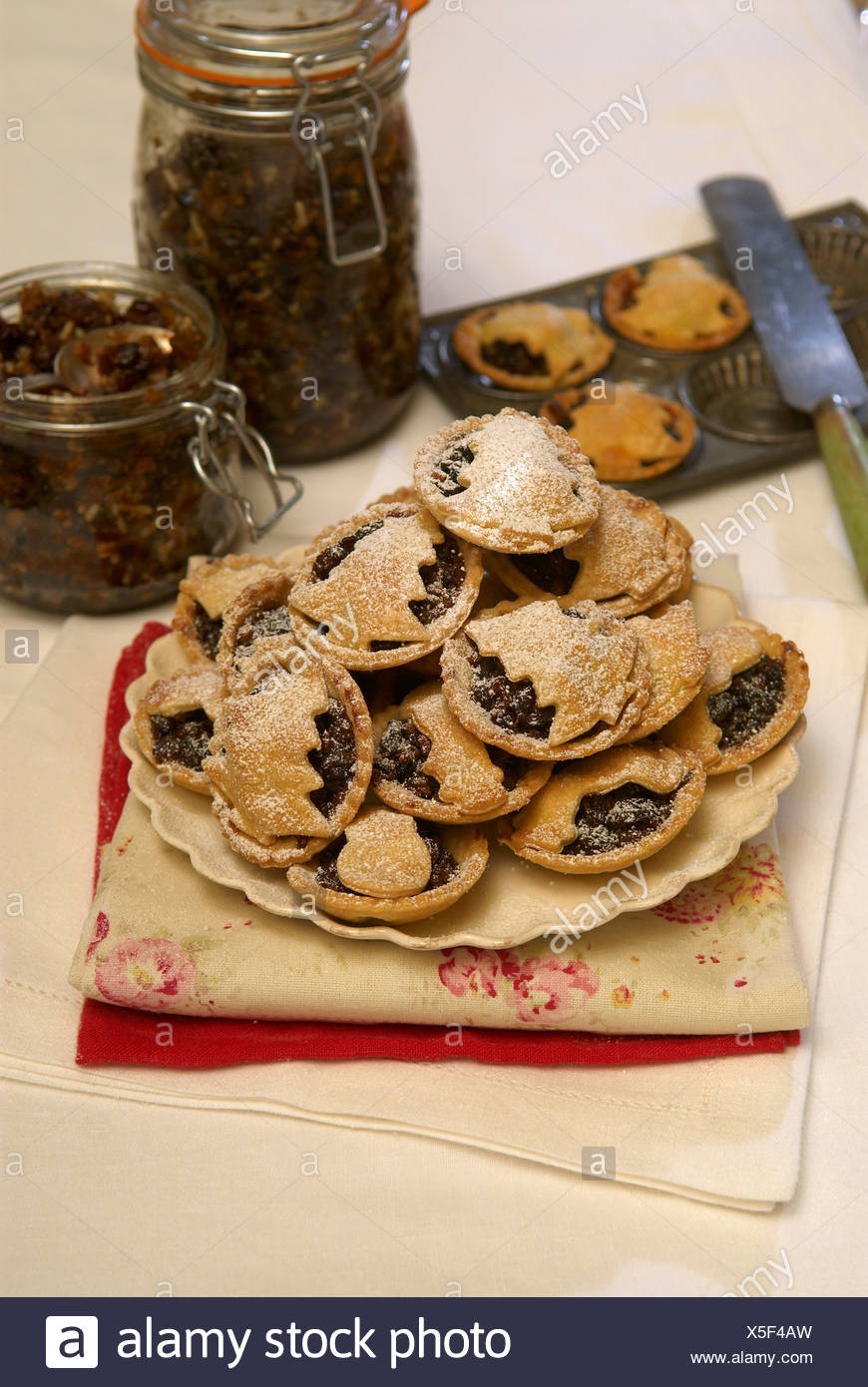 Mince pies piled onto a plate and sprinkled in icing sugar - Stock Image