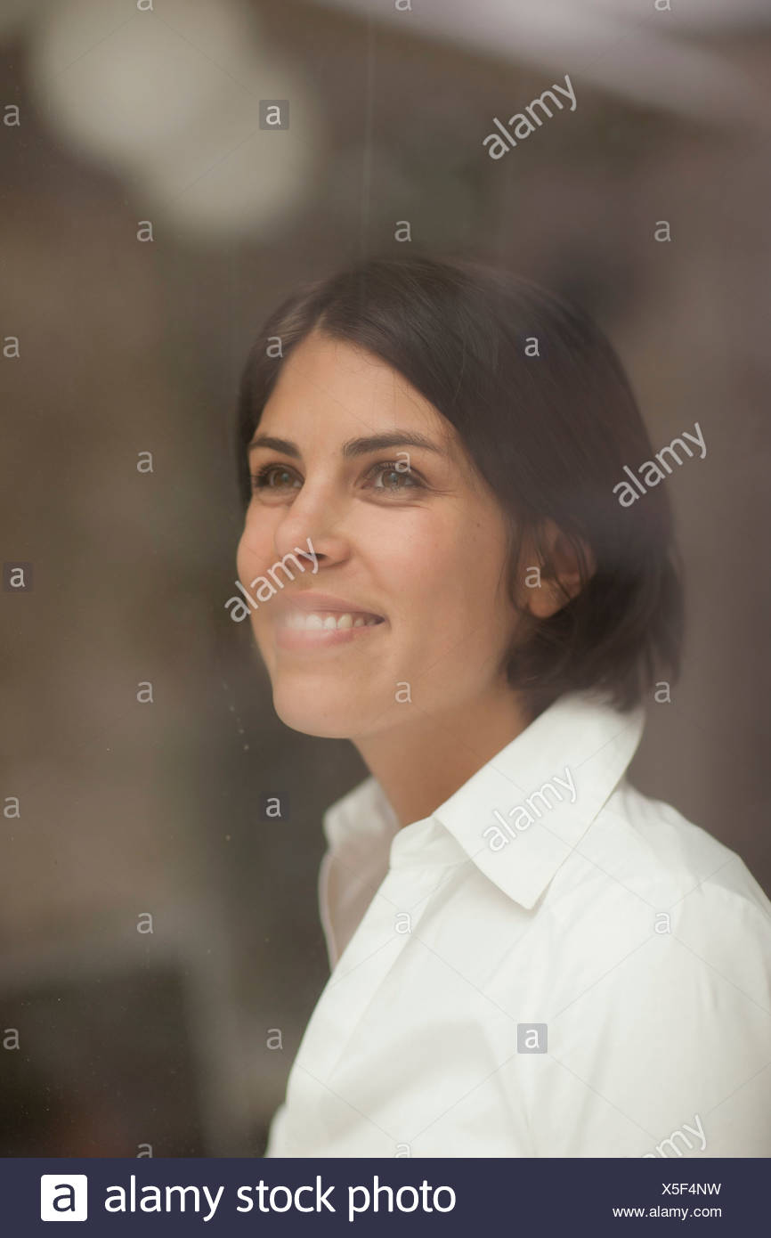 Portrait of young female looking through window - Stock Image