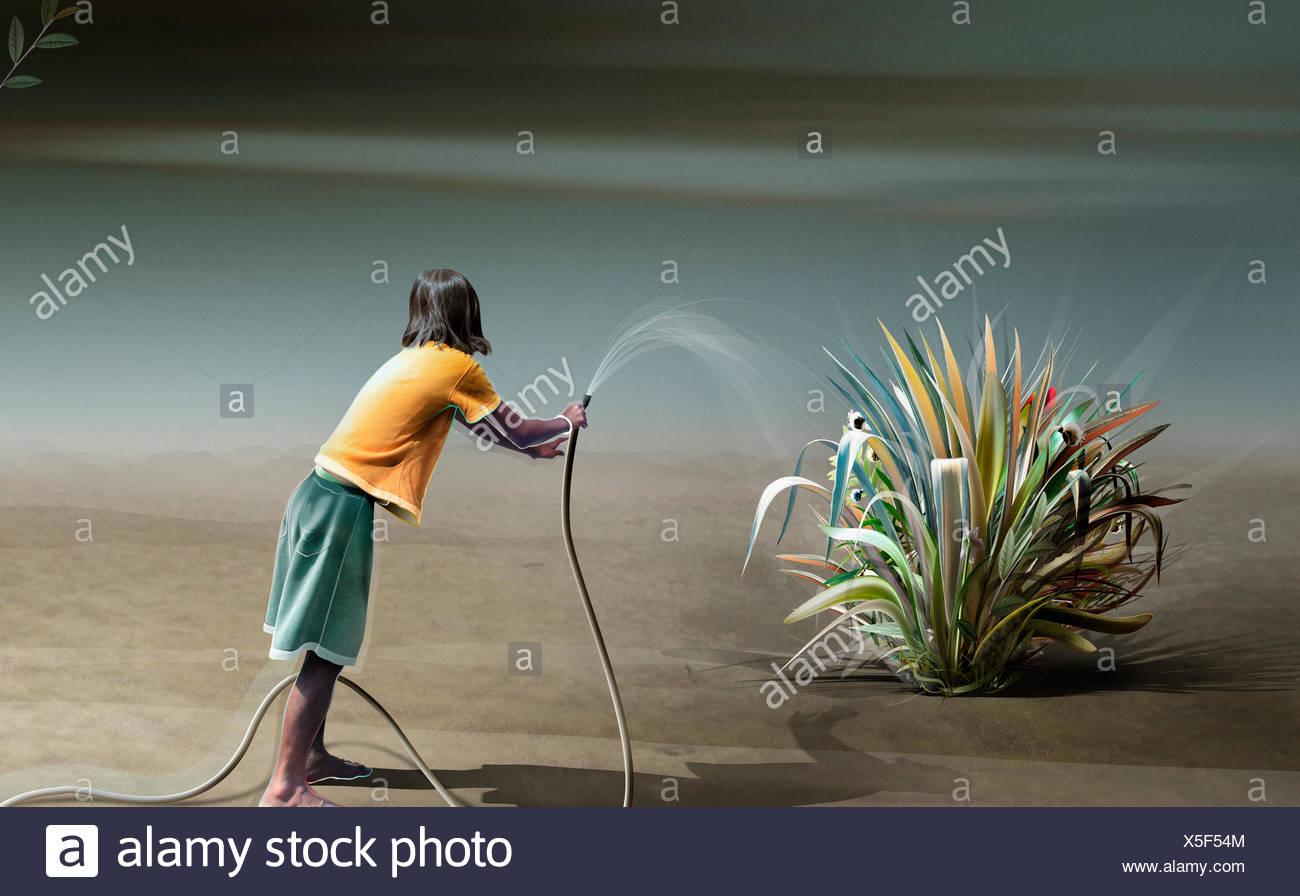 Teenage girl watering plant in desert - Stock Image