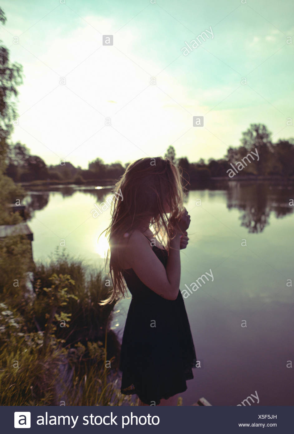 France, Young woman standing at lakeshore - Stock Image