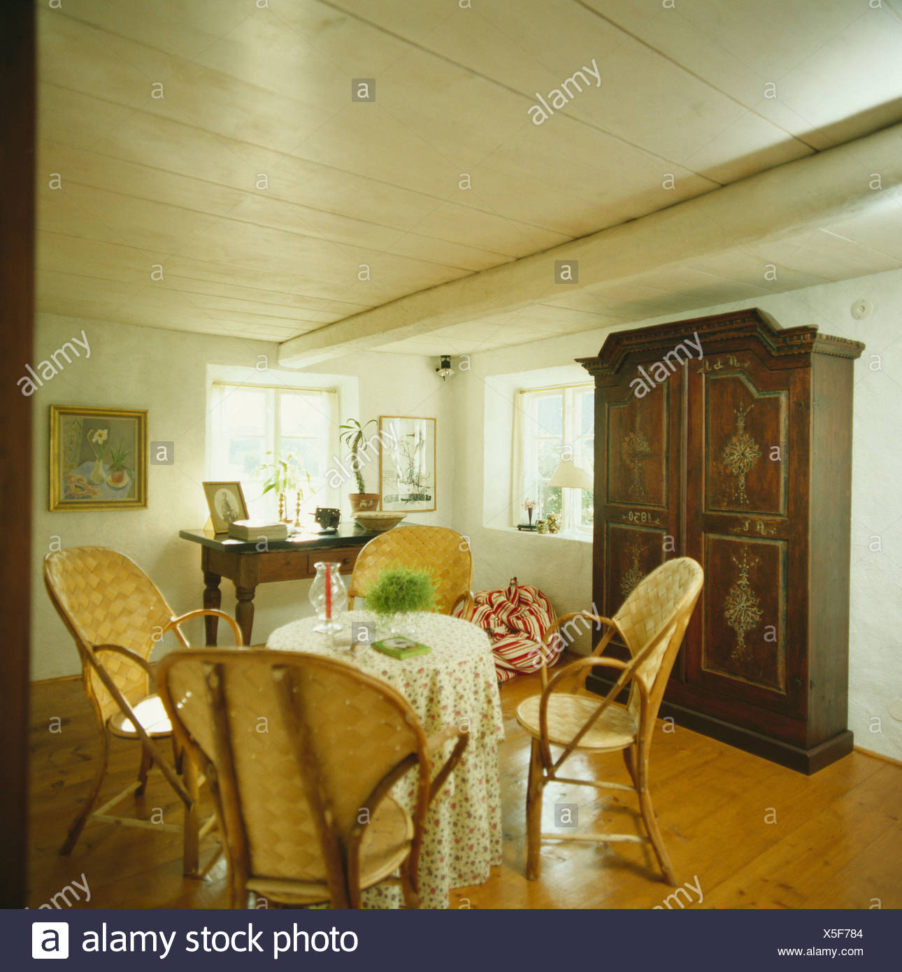 Swedish country diningroom with large cupboard and table with willow chairs on polished wood floor - Stock Image
