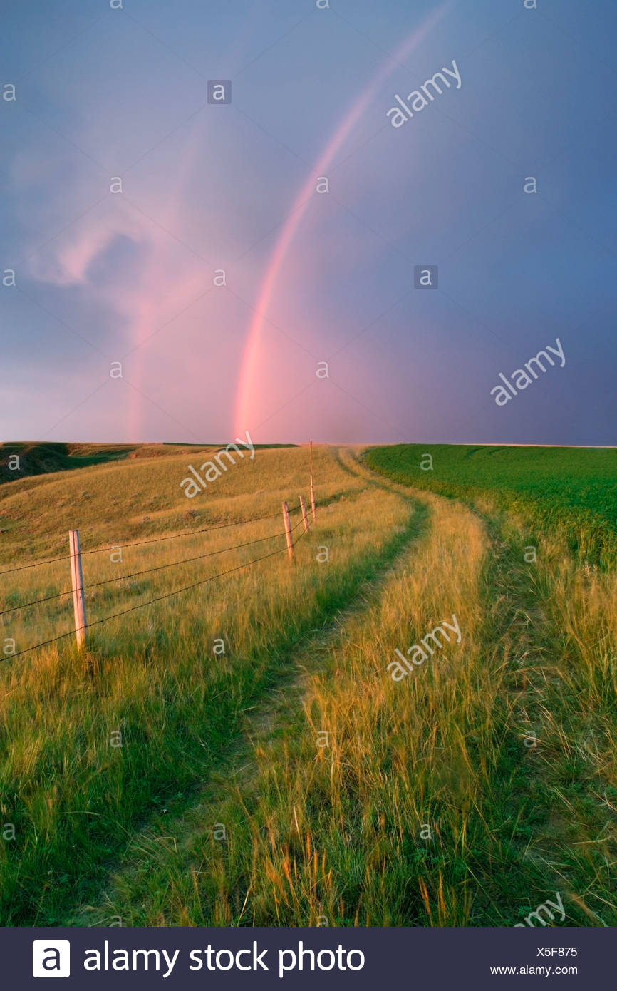 Rucktrail and pastureland and cropland with rainbow near Leader, Saskatchewan, Canada. - Stock Image