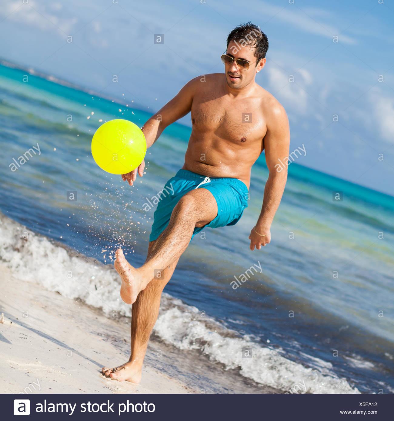 junger lachender mann spielt ball fußball am strand im sommer urlaub freizeit - Stock Image
